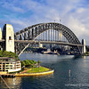 A view of the Sydney Harbor Bridge. At the foot of the south end of the (foreground)  is Sydney's Park Hyatt Hotel and Dawes Point Park.