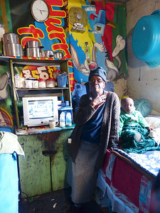 Inside, we visited a small  apartment with 2 bedrooms and talked to this woman. There are 2 beds in the room. One family has one bed and another family has the second. 16 people live in the apartment.