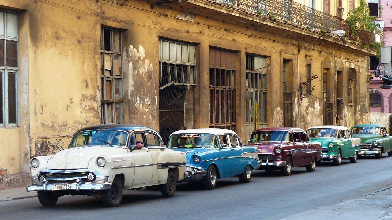 Havana -  Classic cars near the Prado.  These cars are not parked. They are waiting to turn right at a stop sign.