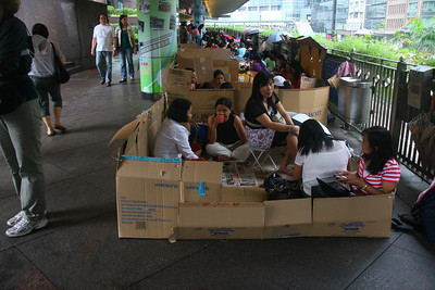 These women are having a holiday in the walkways that connect some of the major buildings on Hong Kong Island. They are Philippino domestic help who work 6 days a week and spend Sundays socializing with their friends.