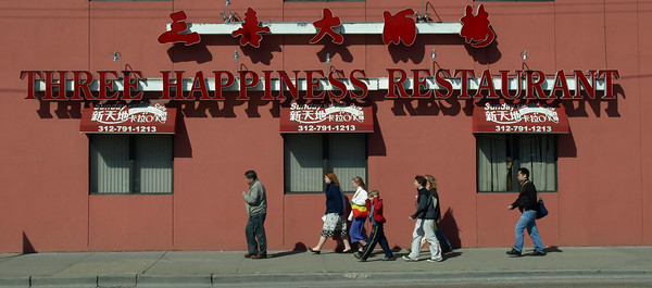 Tourist in front of the Three Happiness Restaurant in China Town