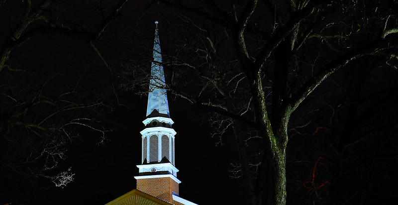 Massive oak trees stand as guardians to a church steeple in Kalamazoo, Michigan on a cold December evening