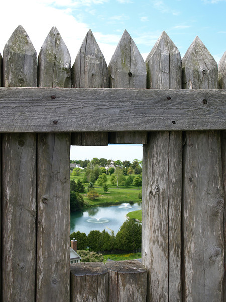 Golf course framed by fence of Fort Mackinac