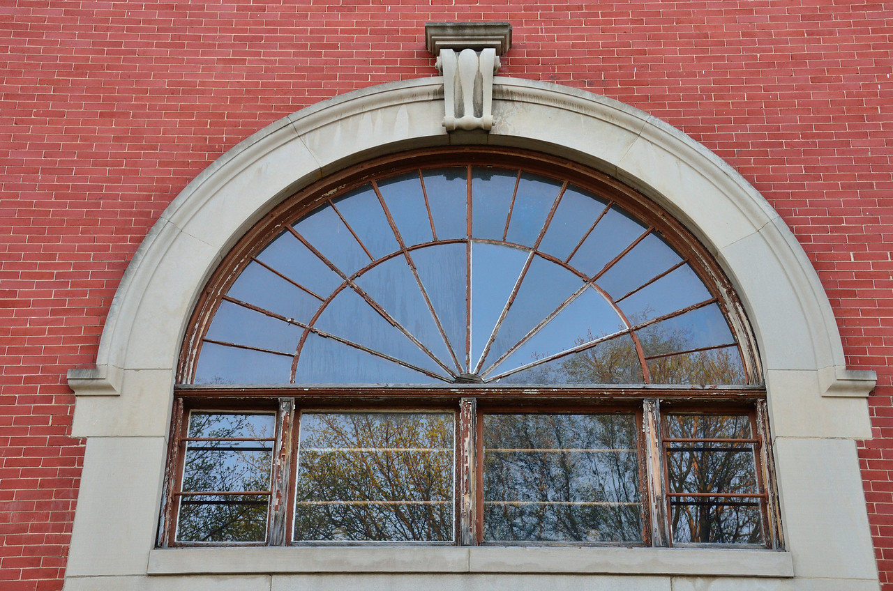 Budding trees are reflected in this archway of glass in the East Hall at Western Michigan University.