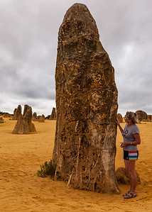 Portrait view of the limestone pinnacle in the Pinnacles National Park, Cervantes, Western Australia with a middle aged women standing next to them giving a sense of scale.