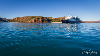 An luxury expedition cruise ship at anchor in the late afternoon in Prince Frederick Harbor on the remote North West Coast of the Kimberley Region of Western Australia.