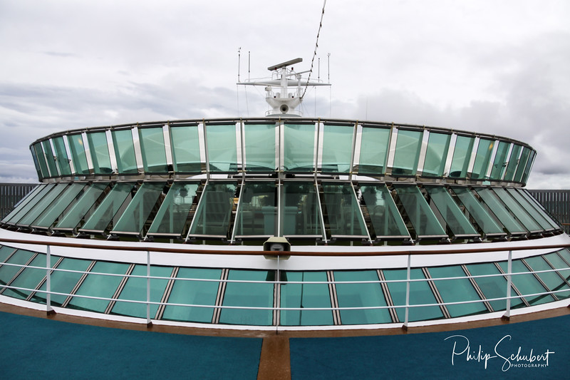 View looking aft showing observation decks of a modern cruise ship.