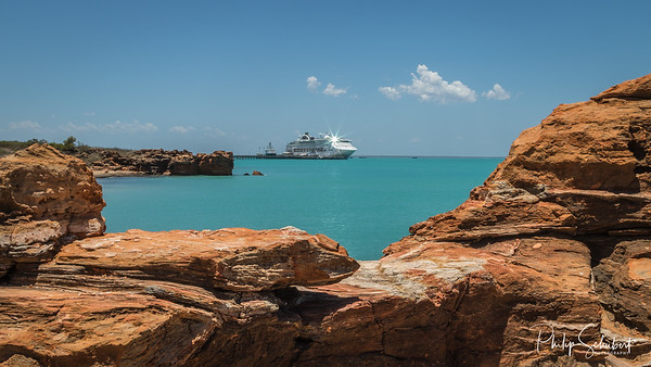 Modern cruise ship tied up to jetty surrounded by a turquoise sea at Broome in Western Australia framed by ochre coloured rocks.