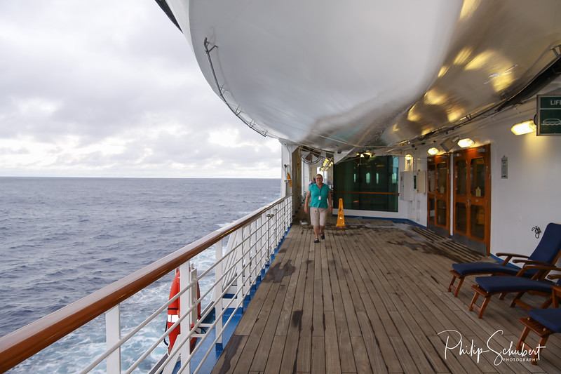 Middle aged woman strolling along teak lined Promenade Deck of modern cruise ship on a grey stormy day.