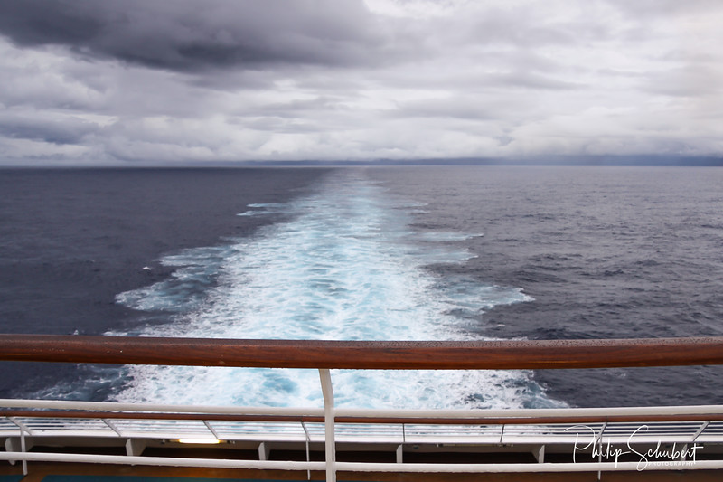 View over stern from upper deck of modern cruise ship showing wake extending into the distance on a grey stormy day in the Tropics.