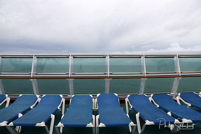 Row of empty deck chairs on the upper deck of a modern cruise ship on a grey and stormy day in the Tropics.