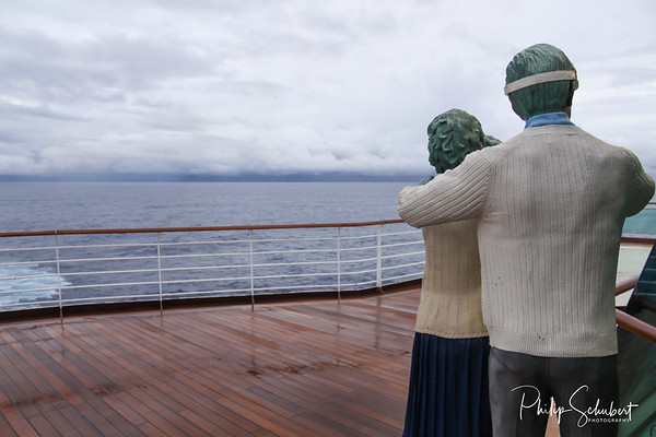 View of two statues looking out to sea from upper deck of modern cruise ship on a grey stormy day in the Tropics.