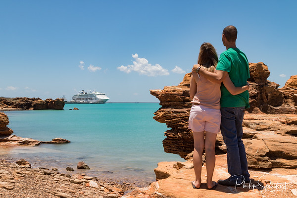 Young couple looking at modern cruise ship tied up to jetty surrounded by a turquoise sea at Broome in Western Australia framed by ochre coloured rocks.