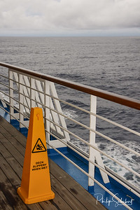 Safety warning marker Teak lined Promenade Deck of modern cruise ship on a grey stormy day.