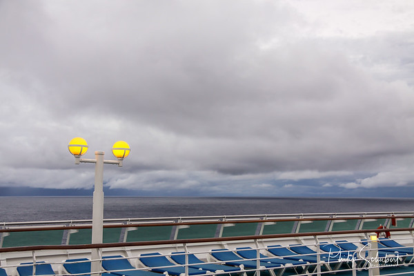 View from upper deck of modern cruise ship with deck chair in the foreground on a grey stormy day in the Tropics.