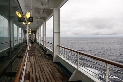 Teak lined Promenade Deck of modern cruise ship on a grey stormy day.