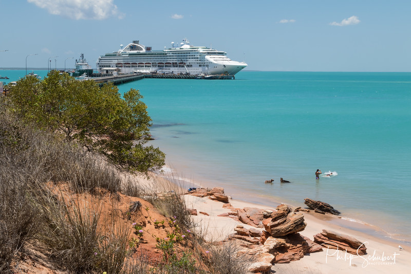 Couple swimming with dogs modern cruise ship tied up to jetty surrounded by a turquoise sea in the background at Broome in Western Australia.