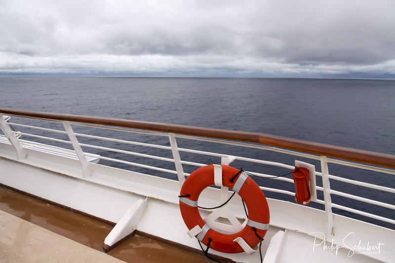 View from upper deck of modern cruise ship showing lifesaver ring and teak railings on a grey stormy day in the Tropics.
