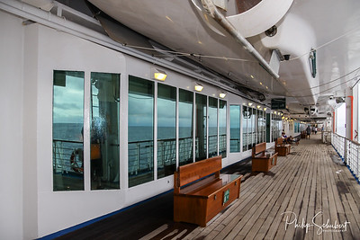 Teak bench and teak lined Promenade Deck of modern cruise ship on a grey stormy day.