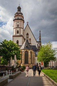 Leipzig, Germany - May 3, 2019: Tourists walk near the famous Thomaskirche where composer Johann Sebastian Bach was a kapellmeister in the 18th century