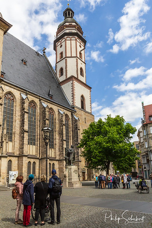 Leipzig, Germany - May 3, 2019: Tourists admire the commemorative statue of the famous composer Johann Sebastian Bach at Thomaskirche where he was a kapellmeister in the 18th century