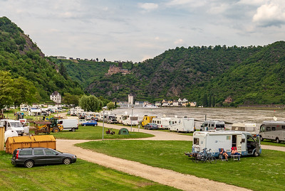 Loreley, Germany - May 24, 2019: Caravans and recreational vehicles camp on the banks of the Rhine River in the Rhine River Gorge opposite the historical Loreley Rock.