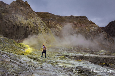 Landscape view of a hiker exploring the sulphur fumaroles and hot mud springs on edge of crater - White Island, New Zealand.