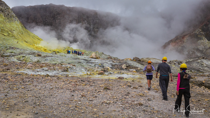 Wide angle landscapeview of tourists hiking towards the active vents in the crater of White Island Volcano, New Zealand.