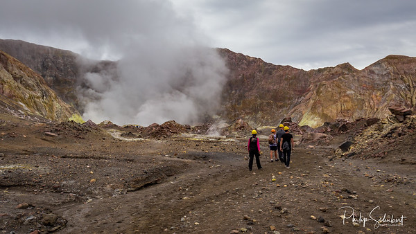 Wide angle landscape view of tourists hiking towards the active vents in the crater of White Island Volcano, New Zealand.
