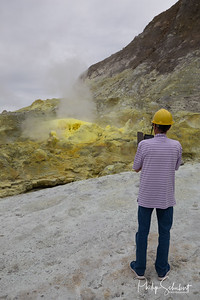 Tourists photograph sulphur fumaroles and hot mud springs on edge of crater - White Island, New Zealand.