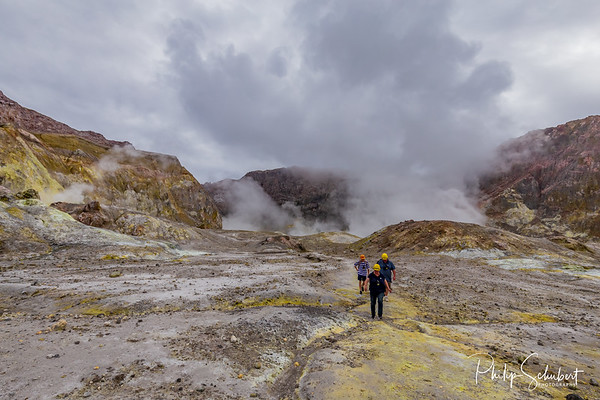 Tourists hiking away from the active vents in the crater of White Island Volcano, New Zealand.