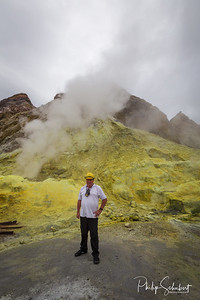 Portrait view of man in hard hat and gas mask standing next to Sulphur Fumeroles and hot mud springs on edge of crater - White Island, New Zealand.