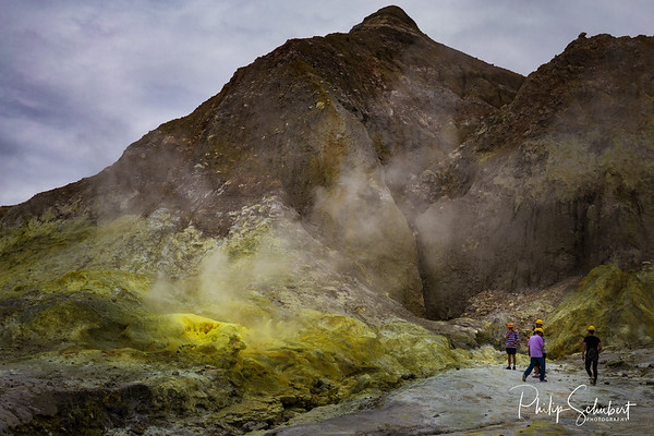 Tourists in hard hats and wearing gas masks stand by sulphur fumaroles and hot mud springs on edge of crater - White Island, an active volcano in the Bay of Plenty, New Zealand.