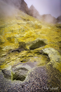 Portait view of sulphur fumaroles, steam vents, sulfataras and hot mud springs on edge of crater at White Island, an active volcano in the Bay of Plenty,  New Zealand.