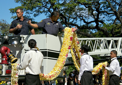 Young Men and Firefighters Lifting Leis