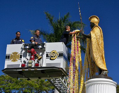 Firefighter Places Leis on the Statue