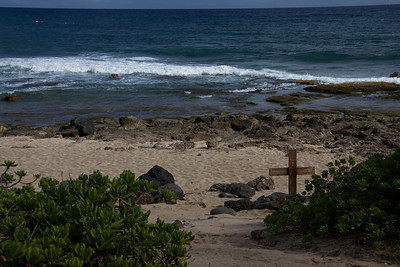 Cross Memorial on Rocky Beach Facing the Ocean