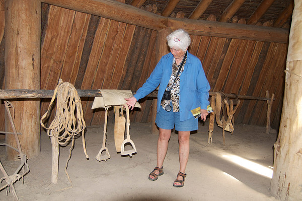 Inside an earth lodge. <br /> <br /> Joel is showing a saddle style used by the indians during the L. and C. period.