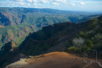 "Waimea Canyon State Park, Waimea Canyon, also known as the Grand Canyon of the Pacific, is a large canyon, approximately ten miles long and up to 3,000 feet deep, located on the western side of Kauaʻi in the Hawaiian Islands of the United States. Waimea is Hawaiian for ""reddish water"", a reference to the erosion of the canyon's red soil. The canyon was formed by a deep incision of the Waimea River arising from the extreme rainfall on the island's central peak, Mount Waiʻaleʻale, among the wettest places on earth."