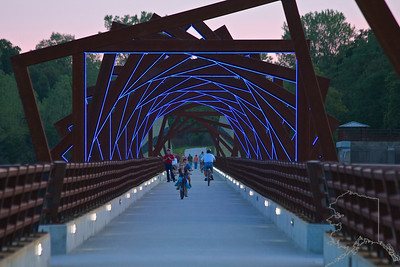 "The High Trestle Bridge. Ever since the grand opening on April 30, 2011 there has been a steady stream of people venturing out to enjoy the scenery. It is ½ mile long, 13-story high Bridge with views reaching 5 miles in both directions. An Iowa artist, David B. Dahlquist, created a vision that weaved in the local coal mining history and regional geology. Steel ""cribs"" reminiscent of a coal mine shaft framed the bridge and four monolithic towers of ""coal and limestone"" formed a gateway. Lighting of the towers, cribs and piers became part of the plan as well. 41 steel ""frames"" over the bridge represent support cribs within an historic coal mine. A must see if you are in Iowa."