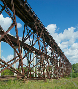 For a long time, this 185' high, quarter mile long span was the highest railroad trestle in the world. It's named after Kate Shelley, a 17-year-old girl who on July 6, 1881 crawled across the wooden original during a storm to warn an approaching passenger train that another trestle downtrack had been washed out. She crawled the span on hands and knees with only lightning for illumination. Once across, she ran a half-mile to the Moingona depot to sound the alarm.The railroad built a new steel bridge in 1900, and named it after her. This is that Bridge. Original steel on one side and new concrete/steel on the other side.