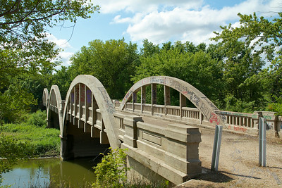 "Known locally as the Lake City Bridge, this concrete Marsh arch bridge spans the North Raccoon River in the southwestern corner of Calhoun County. Consisting of three 80-foot concrete spans supported by a concrete substructure, the bridge's overall length is 271 feet. The bridge dates from 1913, when the Calhoun County Board of Supervisors decided to replace the existing Zane Bridge, a pinned Pratt through truss built in 1892 by the King Bridge Company. The supervisors requested a design for a replacement structure from the state highway commission, which in January 1914 completed the drawings for a three-span pony truss bridge on concrete piers and abutments. At this time, the county also commissioned Des Moines engineer James Marsh to design a three-span concrete arch for the crossing. Marsh's plans featured the through arch design that he had developed two years earlier, with his trademark slotted guardrails and paneled concrete bulkheads. After Marsh's design was approved by the state highway commission in March 1914, competitive bids were solicited on both designs. In April a contract was awarded to the Iowa Bridge Company to build the concrete arch version for the Lake City Bridge for $10,970--some $2000.00 below the amount estimated by the county engineer. IBCo began work on the substructure soon thereafter, eventually shipping in five carloads of cement and three carloads of steel and using some 1000 cubic yards of gravel obtained from a nearby riverbank, according to local sources. The Lake City Bridge was the third of Marsh's namesake rainbow arch bridges built in Iowa. As he would for other bridges in the state, Marsh offered his design to Calhoun County as an alternative to the standard engineering of the state highway commission. It would also serve as a demonstration of his arch in a multiple-span configuration. ""This bridge is being made as a sample,"" the Lake City Graphic reported in 1914. At the time of its completion later that year, Marsh boasted that it was ""the largest bridge of its type in the United States."" The Lake City Bridge is historically significant on a local basis as an important crossing of the North Raccoon River in southwest Calhoun County. In a broader scope, it is technologically significant as a formative exercise in the career of one of Iowa's most distinguished engineers, James B. Marsh. The Lake City Rainbow Arch Bridge is distinguished among these by its early construction, its multiplicity of spans and its formative role in the development of this indigenous structural type abandoned in 1985; remain in a county"