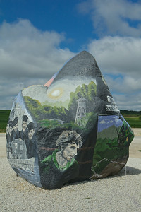 "Every year, for the last nine years, a talented artist, Ray (Bubba) Sorensen II, has done a Memorial Day tribute to our servicemen and servicewomen, both past and present, with a stirring tableau painted on a large granite boulder which stands next to Highway 25. The huge granite boulder came out of the nearby Schillberg Rock Quarry and it weighs approx. 56 ton (50.8Mg) and is 12 ft (3.7m) high.      For years this boulder was known as ""the graffiti rock"" and was decorated for high school rivalries, love interests, etc. Since the Memorial Day paintings began, the ""rock"" has remained with the annual tribute intact.      When Sorensen was 19, he saw 'Saving Private Ryan' and he felt that patriotism was at an all time low and was not being taught in our schools and this motivated him to paint the rock. People were always driving by to see what was painted on the rock. Sometimes there were bad things and other times is was good. He knew if he painted the rock a lot of people would see it.      Sorensen paints over the previous years mural with white paint and starts with a black canvas. He draws a sketch of his idea on paper and then draws the design by free hand onto the rock. This takes him anywhere from one to three weeks to paint. He gets his ideas from books, movies, previous artwork and images by other artists.      If you are anywhere close, you shouldn't miss the opportunity to see what is truly an American treasure."