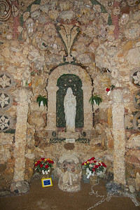 "Father Paul Dobberstein (1872-1954) started construction of the Grotto in 1912. For 42 years he labored, winter and summer, setting ornamental rocks and gems into concrete. At the time of his death in 1954, his incredible Grotto of the Redemption covered one city block. Matt Szerensce (1894-1979), a parishioner, and Father Louis Greving (1921-2002), his successor, worked side-by-side with Father Dobberstein and furthered the work of Father Dobberstein after his death.The Grotto of the Redemption at West Bend, Iowa, is the largest Grotto in the world. Often called the ""Eighth Wonder of the World"", the Grotto represents a vast collection of minerals and stone— petrified wood, stalactite and stalagmite, malachite, jasper, quartz crystals and many more. Italian Mosaic and Carrara marble statues adorn the geological wonder. The Grotto is listed on the National Register of Historic Places. Adjacent to the Grotto is Sts. Peter and Paul Catholic Church. The Chrismas Chapel in the church is consid- ered to be Father Dobberstein's finest work. It contains a Brazilian amethyst that weighs over 300 lbs. The theme of the Redemption is told in faceted stained glass win- dows in the church. A 22-foot bird's-eye maple, hand carved altar which won first place at the Chicago World's Fair in 1893 graces the sanctuary."