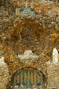 """Father Paul Dobberstein (1872-1954) started construction of the Grotto in 1912. For 42 years he labored, winter and summer, setting ornamental rocks and gems into concrete. At the time of his death in 1954, his incredible Grotto of the Redemption covered one city block. Matt Szerensce (1894-1979), a parishioner, and Father Louis Greving (1921-2002), his successor, worked side-by-side with Father Dobberstein and furthered the work of Father Dobberstein after his death.The Grotto of the Redemption at West Bend, Iowa, is the largest Grotto in the world. Often called the """"Eighth Wonder of the World"""", the Grotto represents a vast collection of minerals and stone— petrified wood, stalactite and stalagmite, malachite, jasper, quartz crystals and many more. Italian Mosaic and Carrara marble statues adorn the geological wonder. The Grotto is listed on the National Register of Historic Places. Adjacent to the Grotto is Sts. Peter and Paul Catholic Church. The Chrismas Chapel in the church is consid- ered to be Father Dobberstein's finest work. It contains a Brazilian amethyst that weighs over 300 lbs. The theme of the Redemption is told in faceted stained glass win- dows in the church. A 22-foot bird's-eye maple, hand carved altar which won first place at the Chicago World's Fair in 1893 graces the sanctuary."""