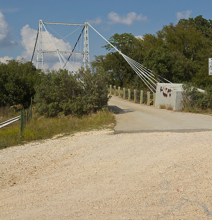 "The Regency Bridge, locally known as the ""Swinging Bridge,"" is a one-lane suspension bridge over the Colorado River in Texas. It is located at the intersection of Mills County Road 433 and San Saba County Road 137, both gravel roads, near a small community called Regency. The bridge saddles the Colorado River between Mills and San Saba counties. The bridge has a span of 325 feet  and a wood surface. It was built in 1939, by the W.P.A. with most of the work being done by hand. The bridge was restored in 1997"