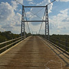 """The Regency Bridge, locally known as the """"Swinging Bridge,"""" is a one-lane suspension bridge over the Colorado River in Texas. It is located at the intersection of Mills County Road 433 and San Saba County Road 137, both gravel roads, near a small community called Regency. The bridge saddles the Colorado River between Mills and San Saba counties. The bridge has a span of 325 feet  and a wood surface. It was built in 1939, by the W.P.A. with most of the work being done by hand. The bridge was restored in 1997"""