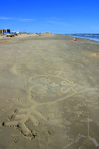 I watched a man draw this in the sand. I took his picture a few times but I think he did not know I was there. After a while he reach into his pocket and pulled out a container. He sprinkled something gray onto the heart looked at it for a while then left. I went over to look and it was ashes he had put there. I am glad I did not infringe on him as he was having a personal moment with a love one. I will never forget taking this picture.