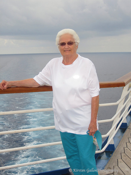 My mom at the aft of the ship with the wake in the background.