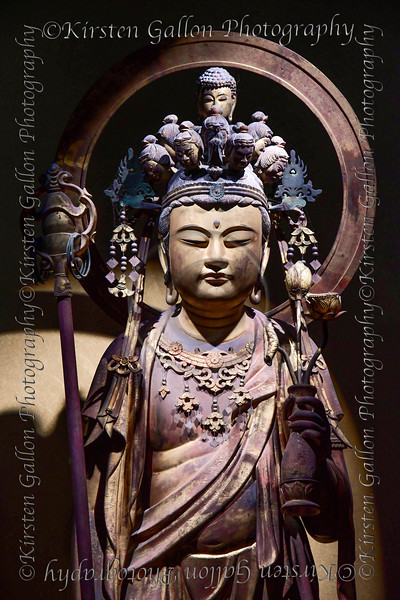 """Standing Juichimen Kannon Bosatsu<br /> Kannon Buddhisattva with Eleven Headed<br /> This statue was enshrined in front of the principal image. It is thought to have its origins in the Edo period, but it is <br /> considered  to  be  a  revival  Buddha  of  an  old  image  that  was  made  in  the  Muromachi  period  from  the  inscribed  <br /> wooden tags placed inside the statue.<br /> The figure with a monk's staff in the right hand is a form specific to the Hasedera Temple called """"Hasedera-style <br /> Juichimen Kannon"""". It constitutes an important clue to consider the history of the principal image."""